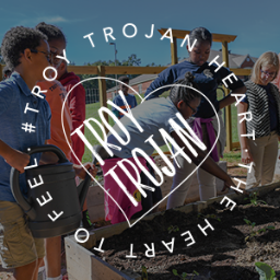 TROY Trojan Heart logo over group of Troy Elementary students working in garden