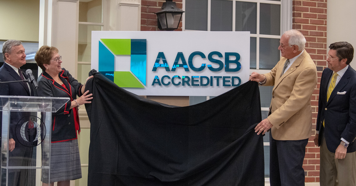 Troy University administrators unveiling the AACSB Accreditation Logo