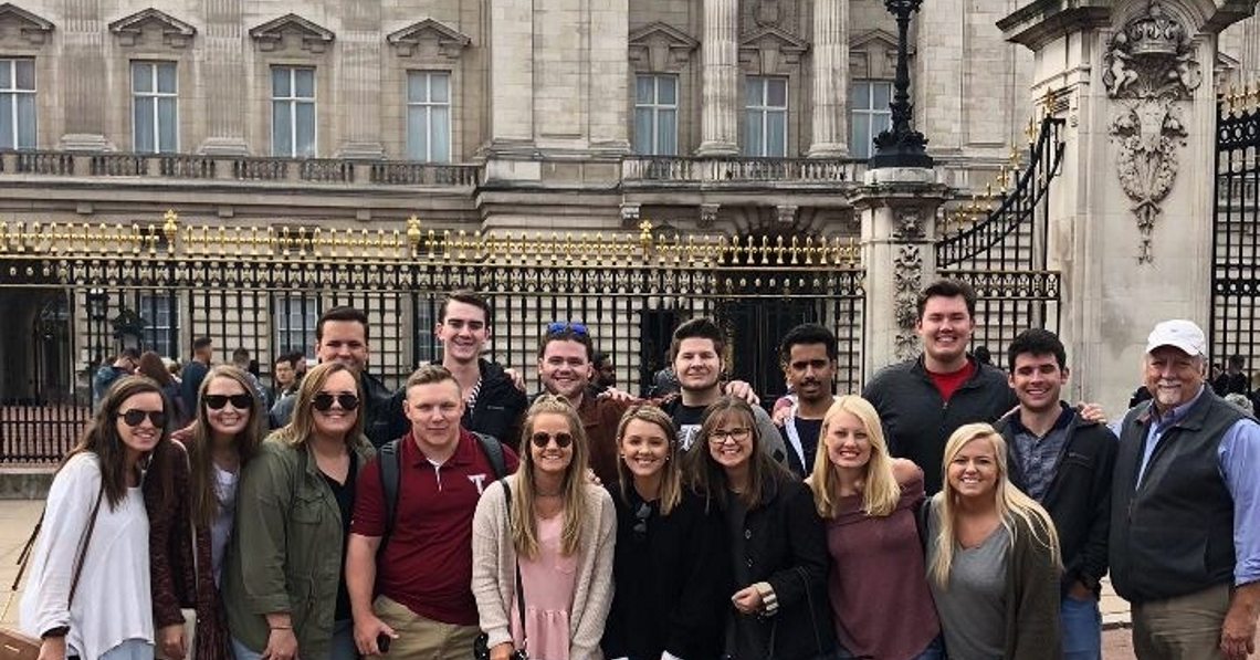 Risk Management and Insurance students on their study abroad trip to London, England posing in front of Buckingham Palace