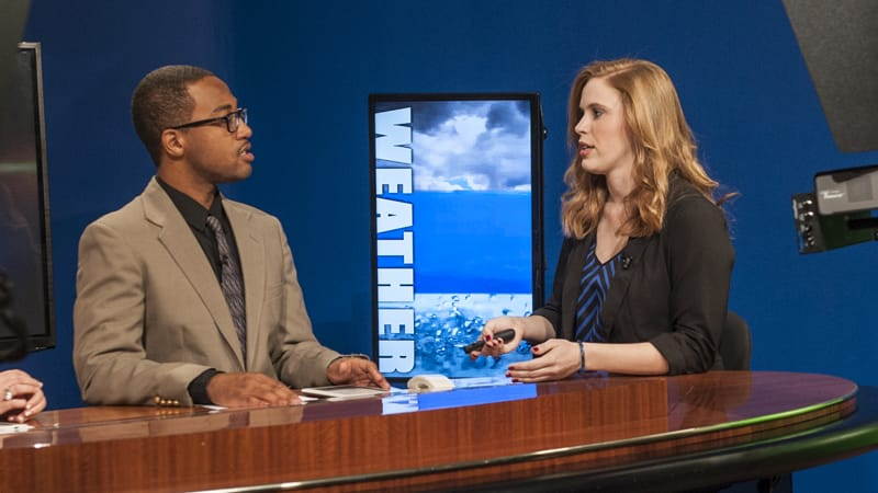 Students Jarmarlo Phillips and Haley Greathouse discuss the weather on TROY TrojanVision News