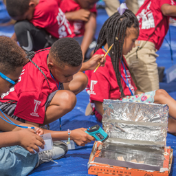 Participants in the Kids at College STEM camp build pizza box ovens.