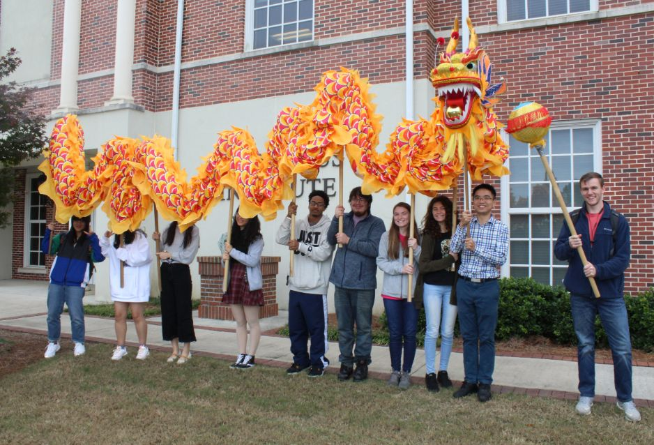 Students pose in a group picture with the dragon used in dragon dances.