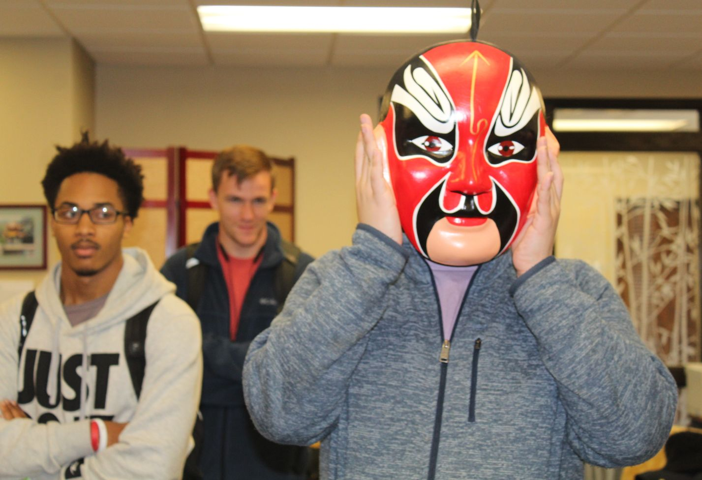A student tries on a Chinese mask.