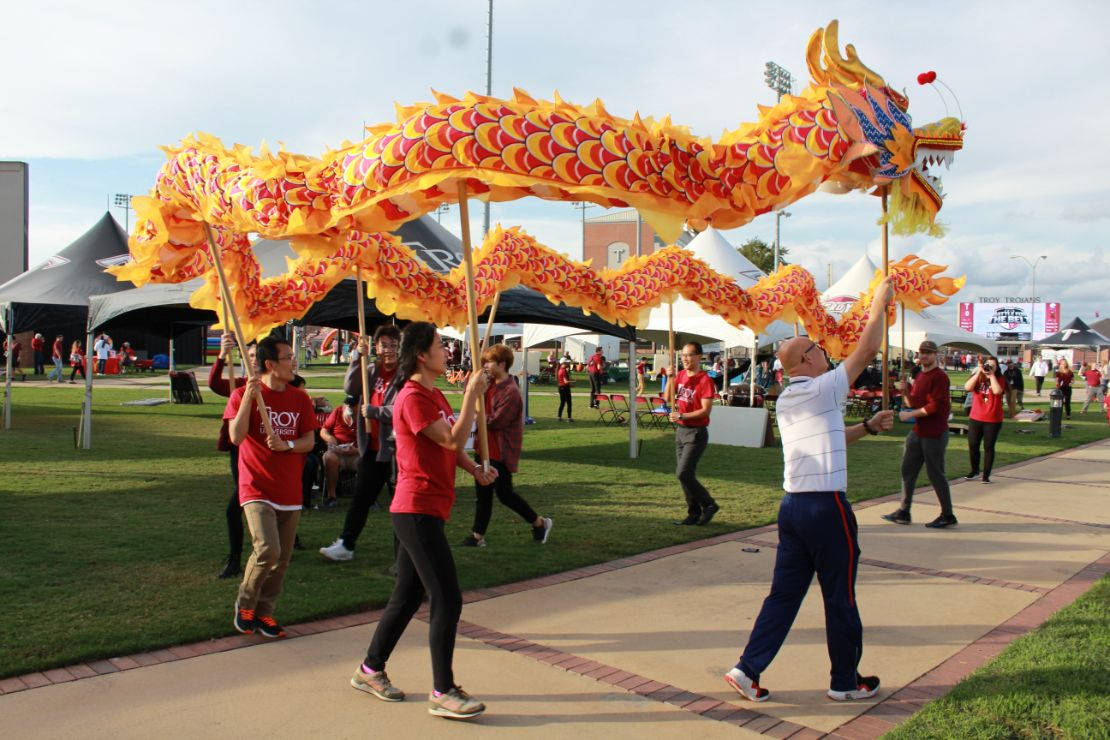 The CIT staff and Visiting Scholars perform the dragon dance with a yellow dragon.