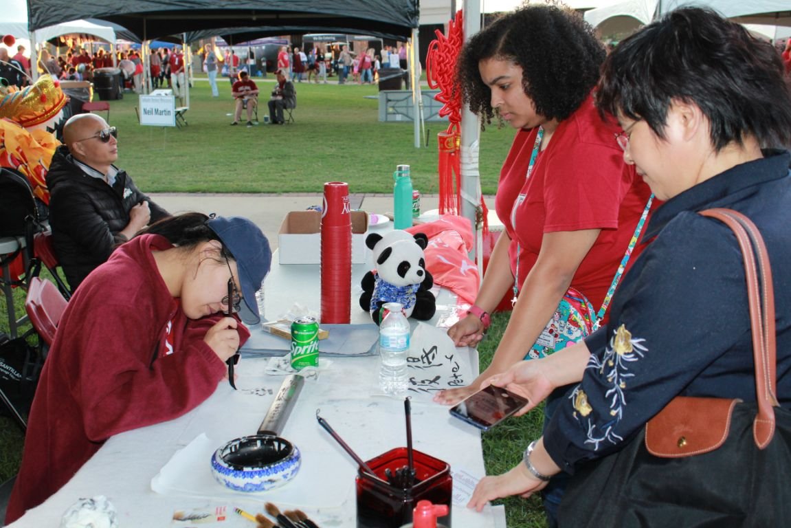 Visiting Scholar, He Jing writes in Chinese calligraphy for tailgate patrons.