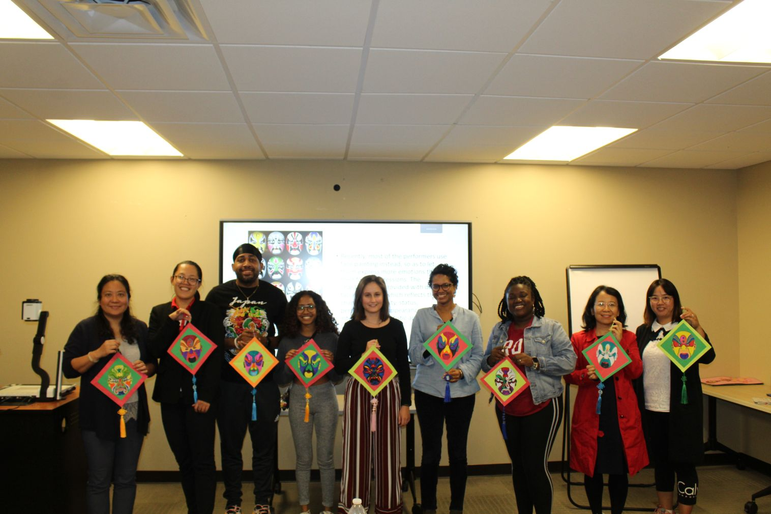 The students and CIT Visiting Scholars pose with their colored opera masks in a group picture.