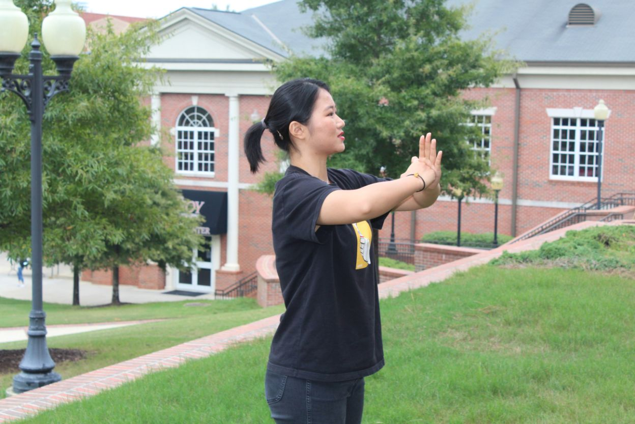 A scholar teaches the participant the peaceful pose with the right fist pressed against the flat of the left palm.