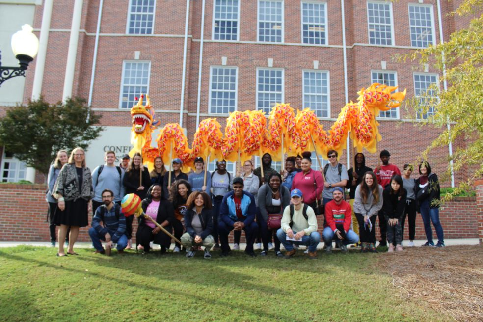 The students pose in group picture, with the yellow dragon propped up behind them.