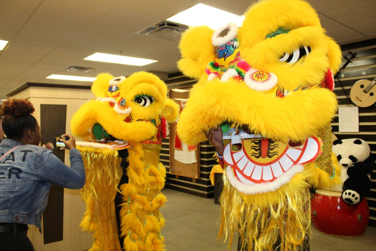 Two students try to put on the yellow lion costume and perform a lion dance.