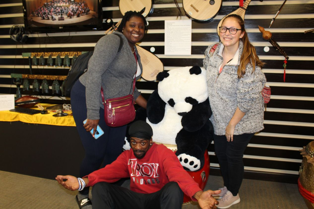 Three students poses with Chinese memorabilia, namely a panda stuffed animal.
