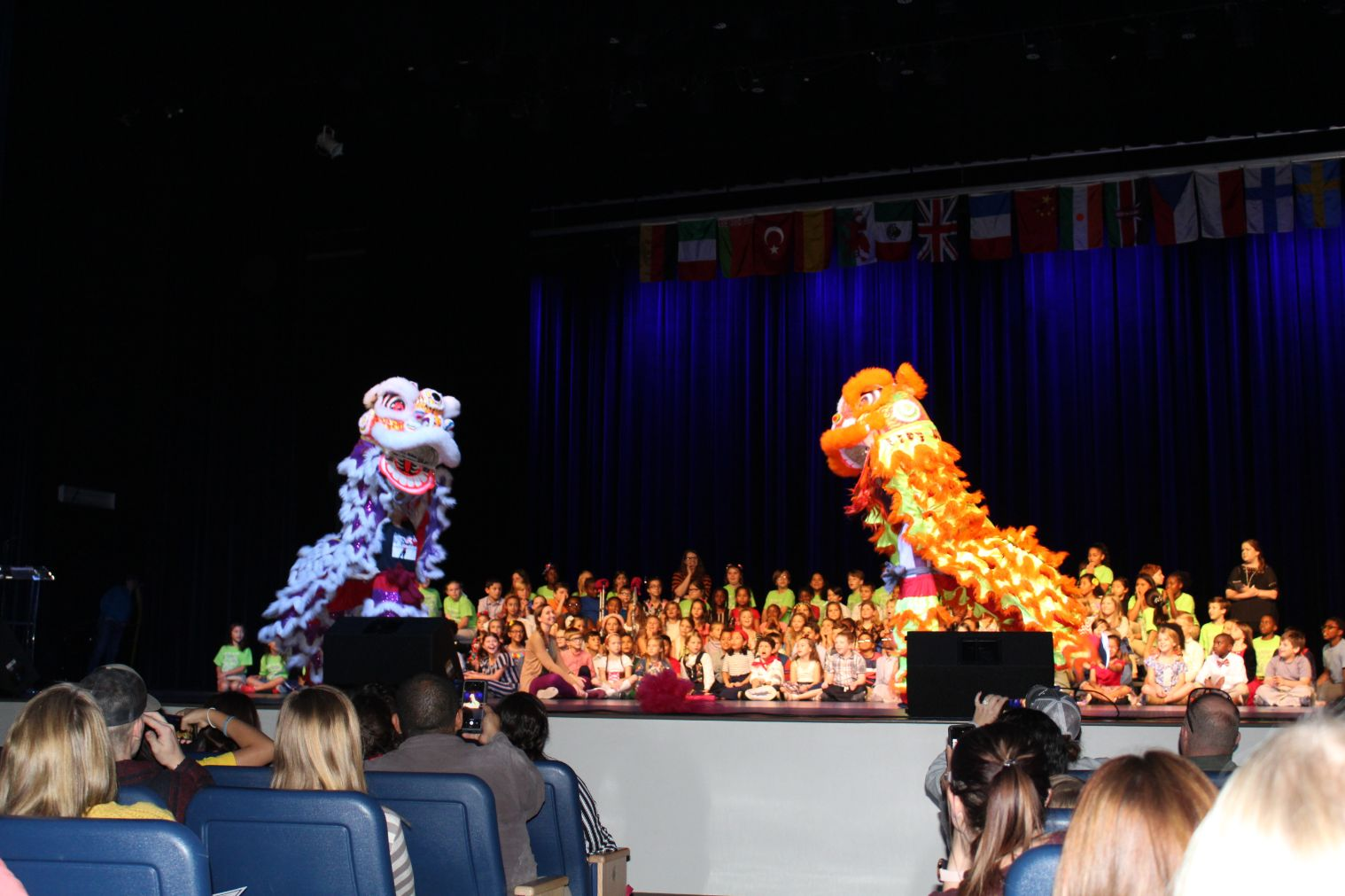 Dancers perform the Twin Lions dance in purple and orange costumes on stage for everyone to enjoy.