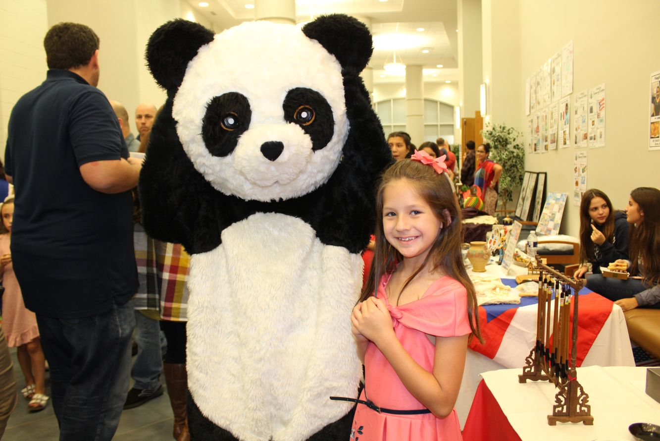 A young girl poses for a picture with the big, fluffy panda bear.