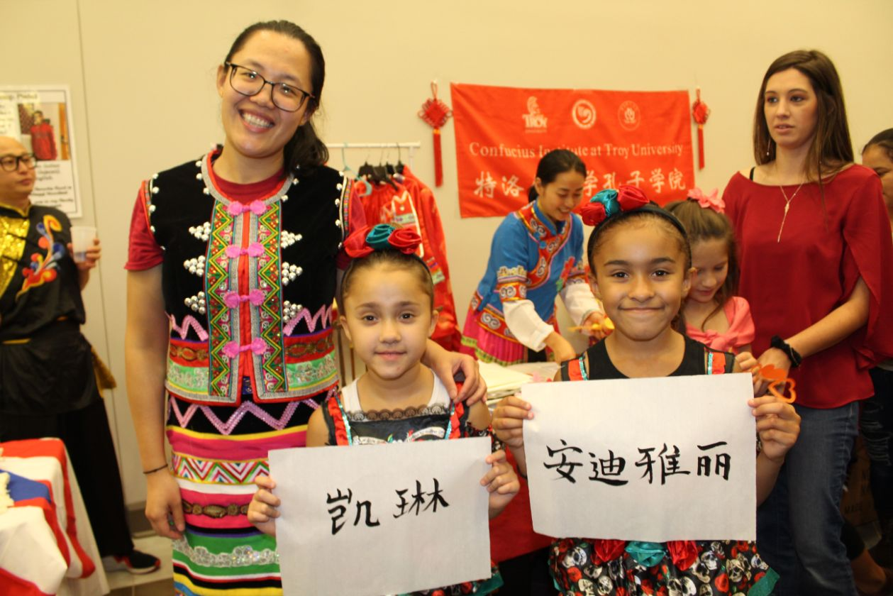 Children pose with Visiting Scholar He Jing, holding their name written in Chinese characters.