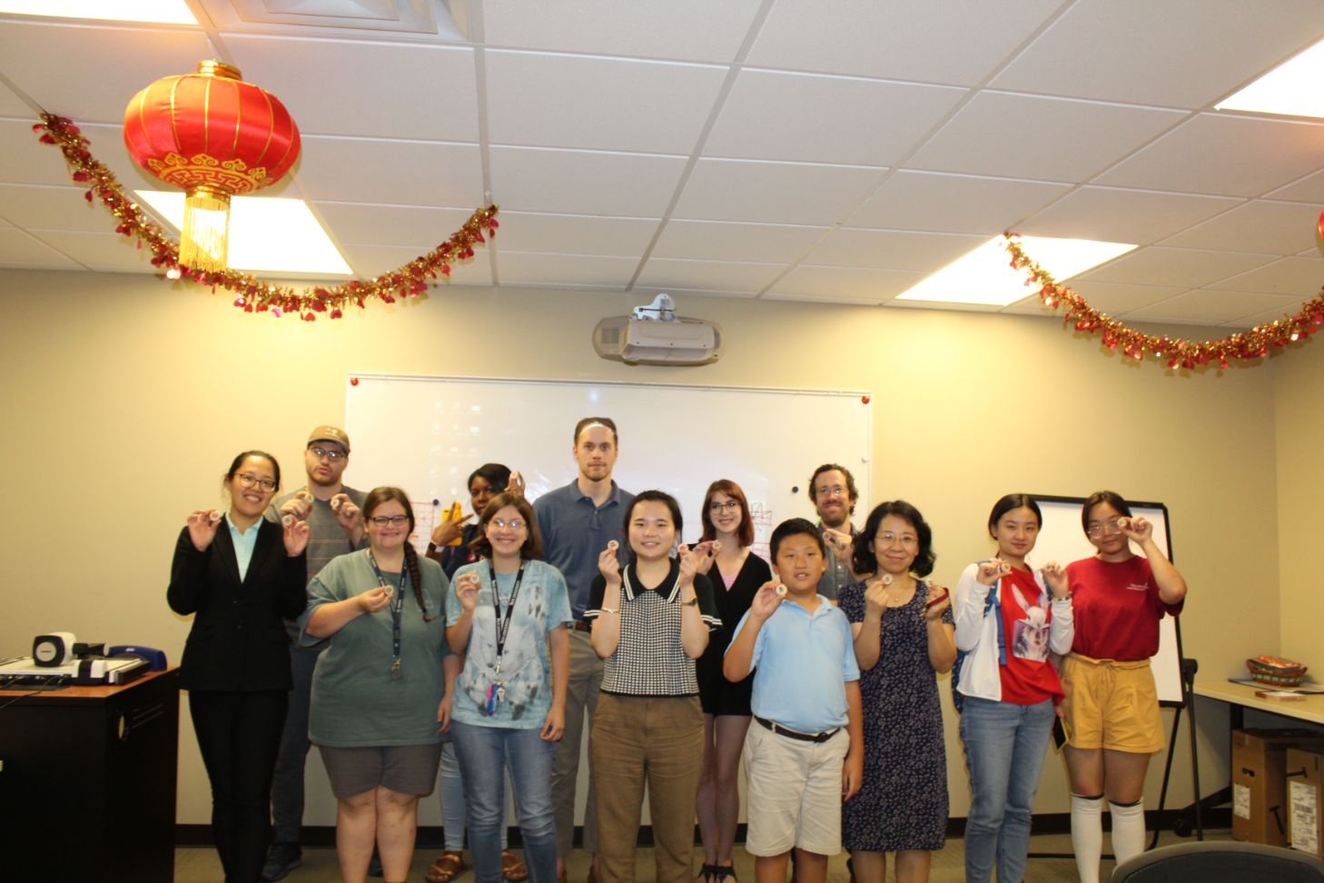 The students and CIT staff pose together with Chinese chess pieces in a group picture.