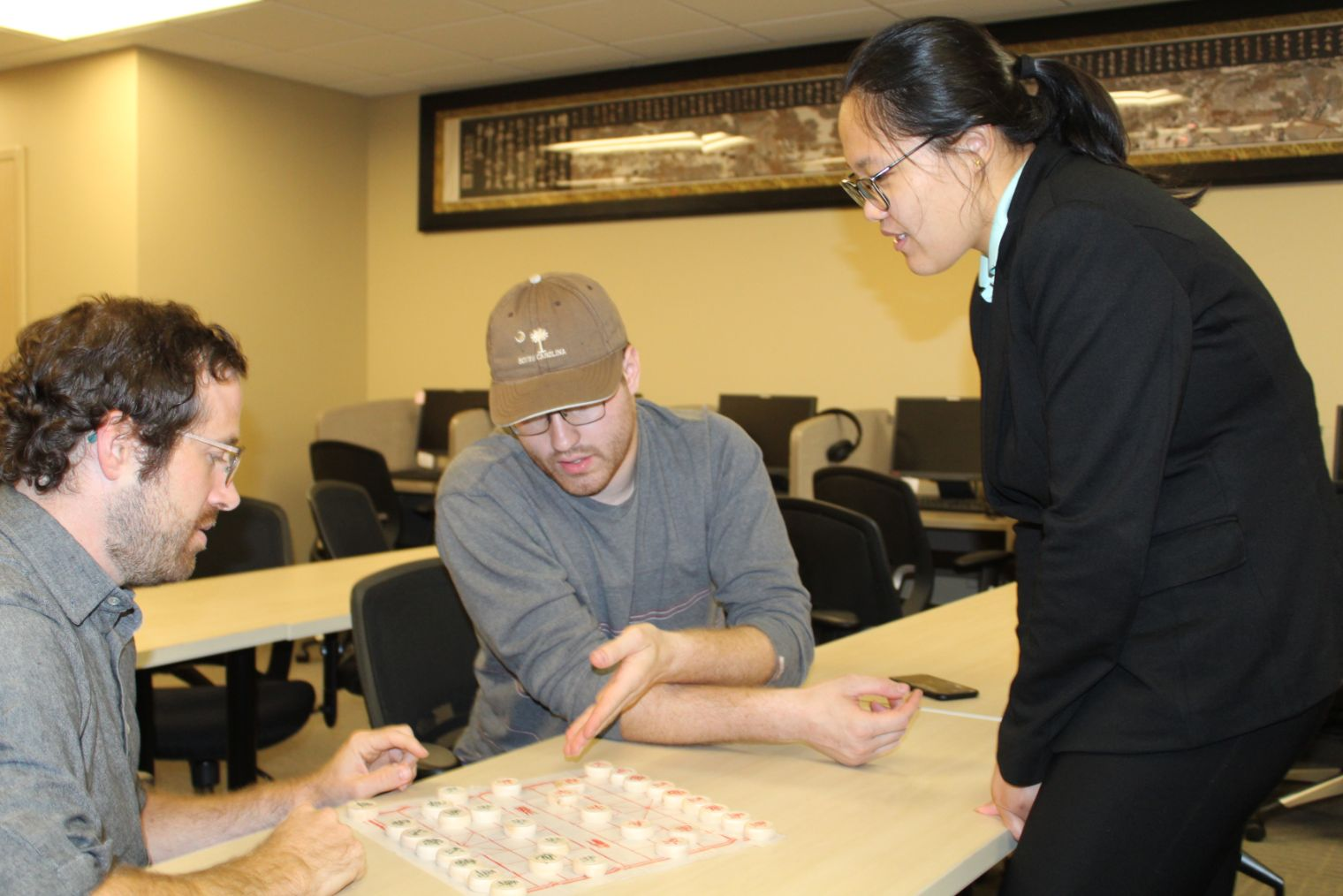 Visiting Scholars help students strategize in a game of Chinese chess.