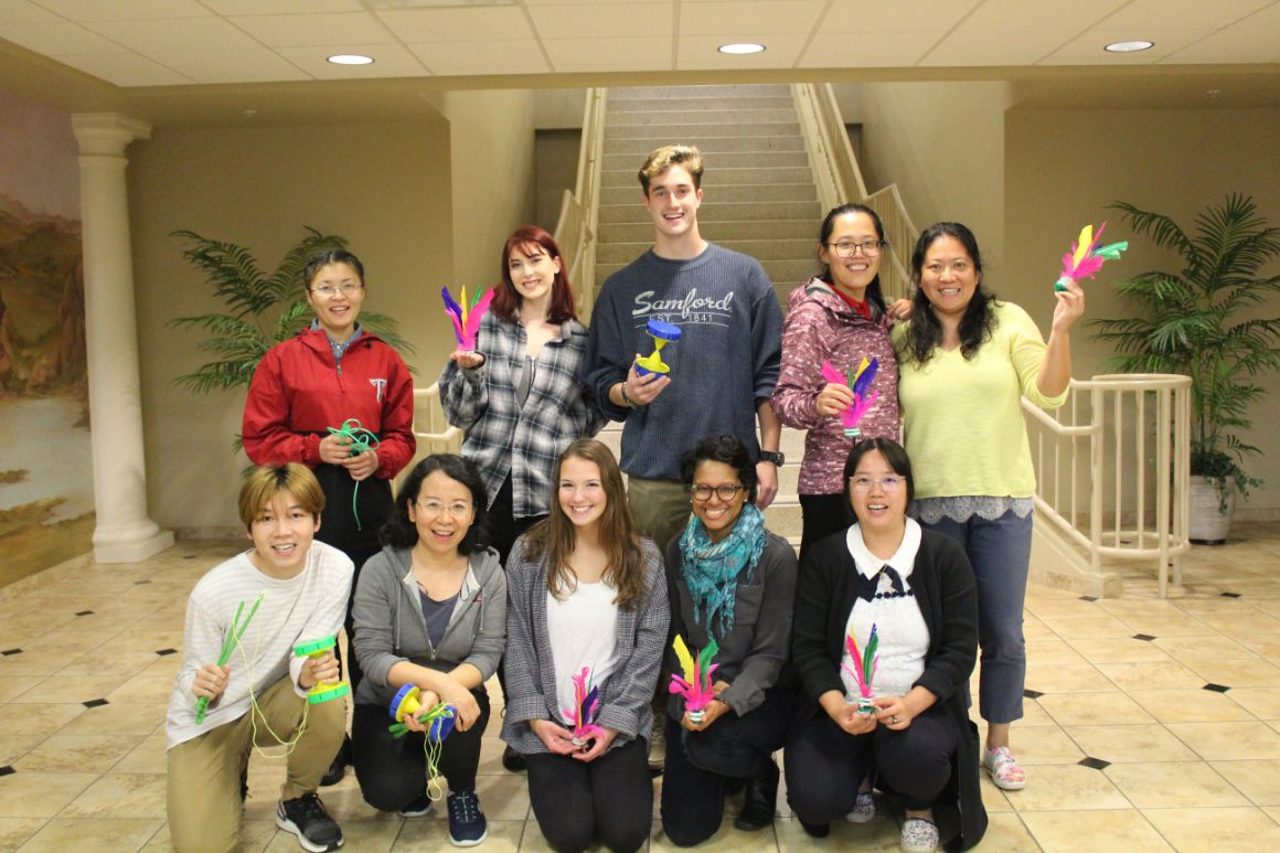 The students and Visiting Scholars pose for a group picture holding their favorite game items.
