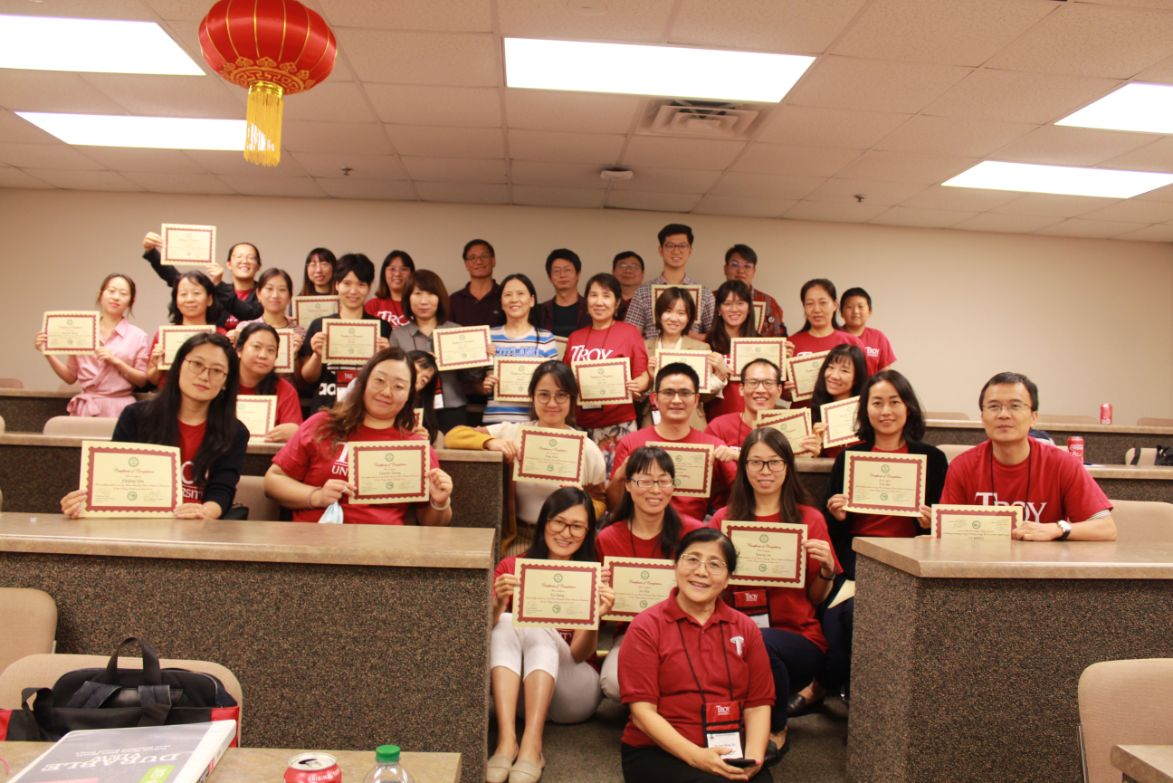 The teachers pose together with their certificates award by Dr. Feng and Dr. Xu.