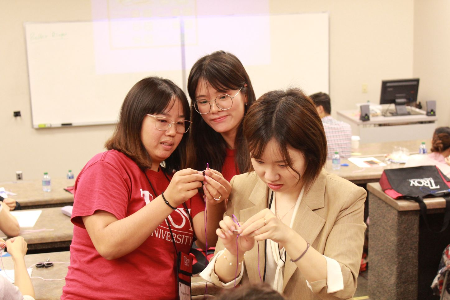 The teachers learn how to make Chinese crafts out of yarn and key chains.