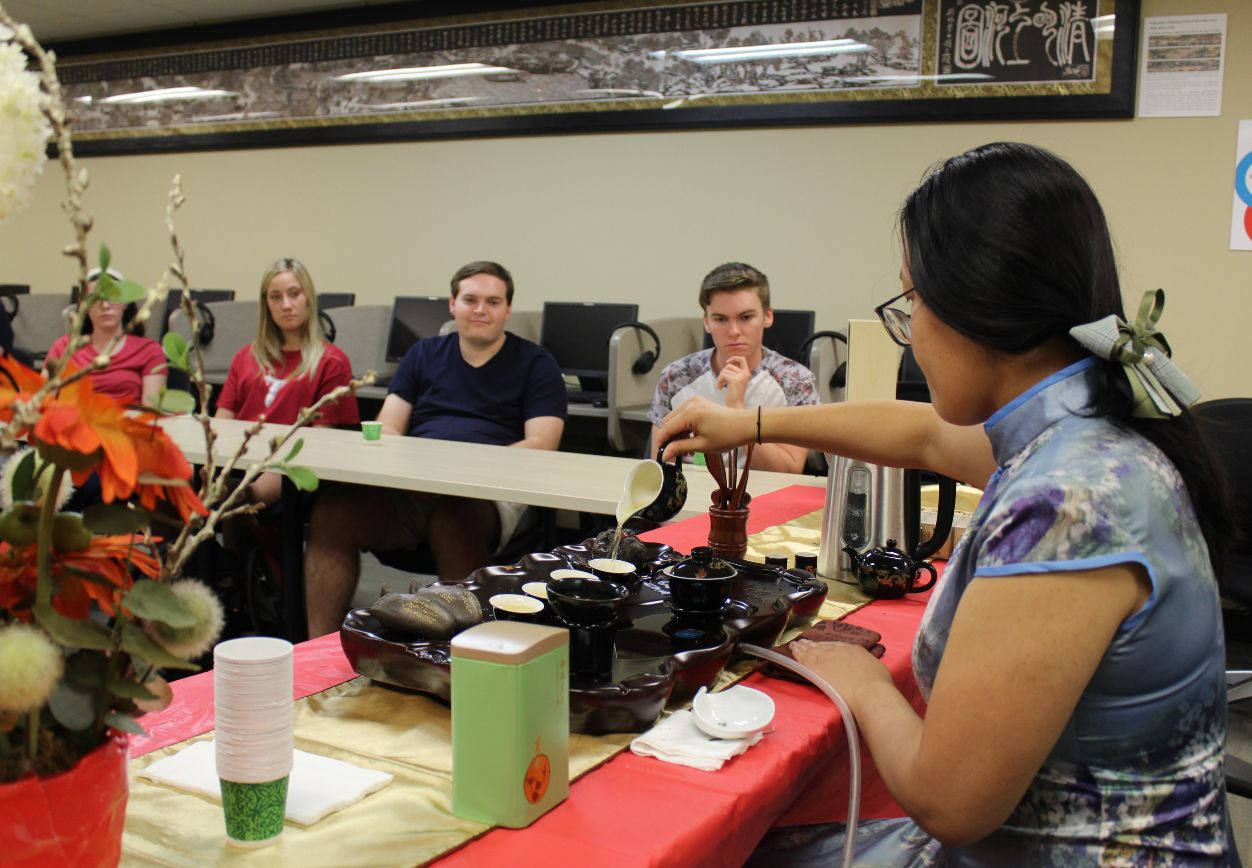 The students watch He Jing pour the traditional Chinese tea.