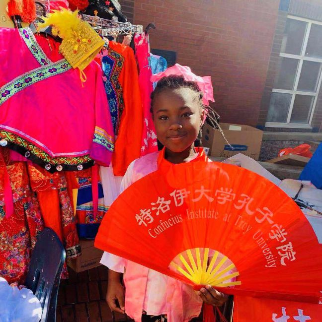 A young girl dresses up in traditional Chinese clothing and poses with a fan.