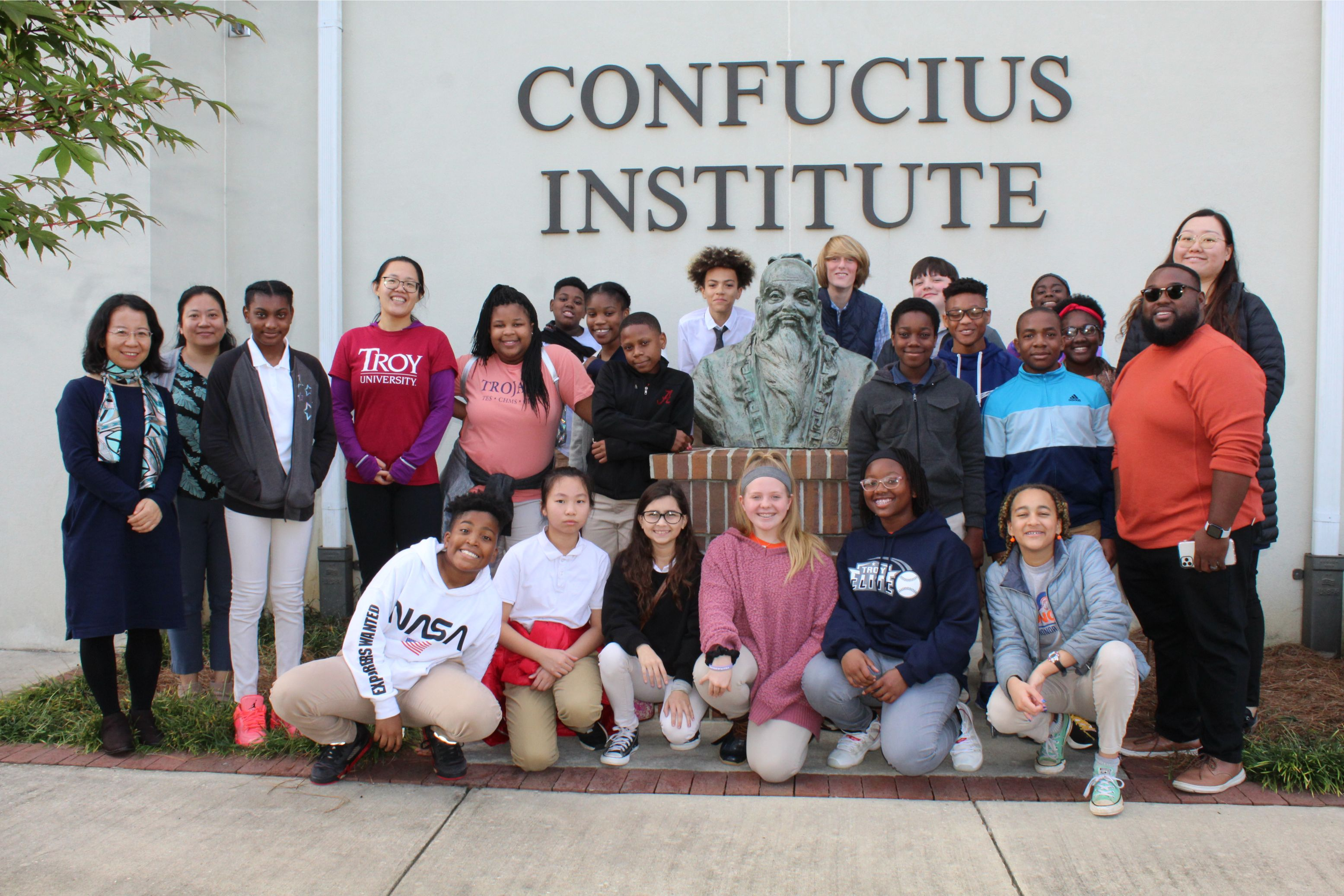 The students pose in a group picture by the Confucius statue outside of CIT.