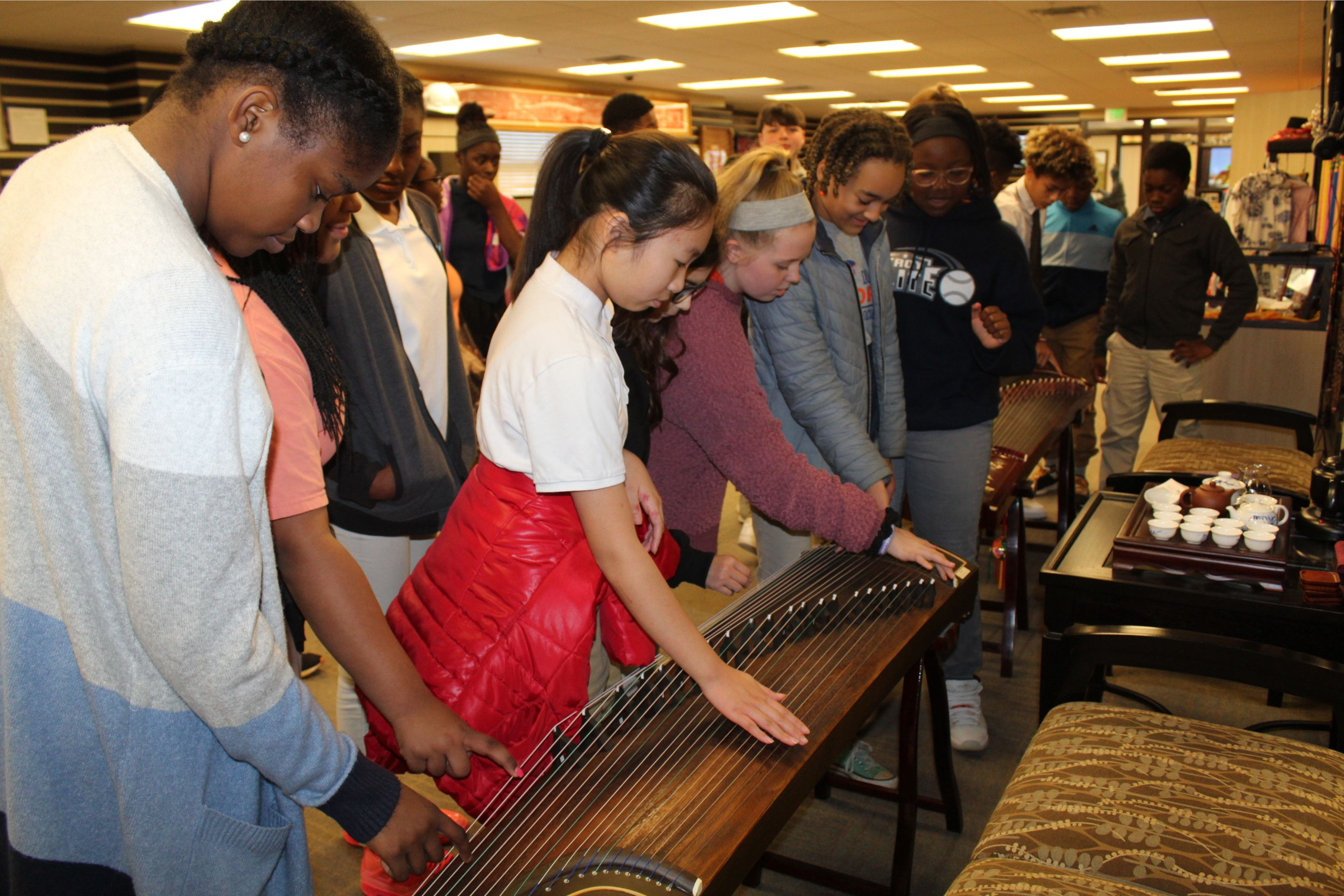 The students reach out to play on the guzheng.