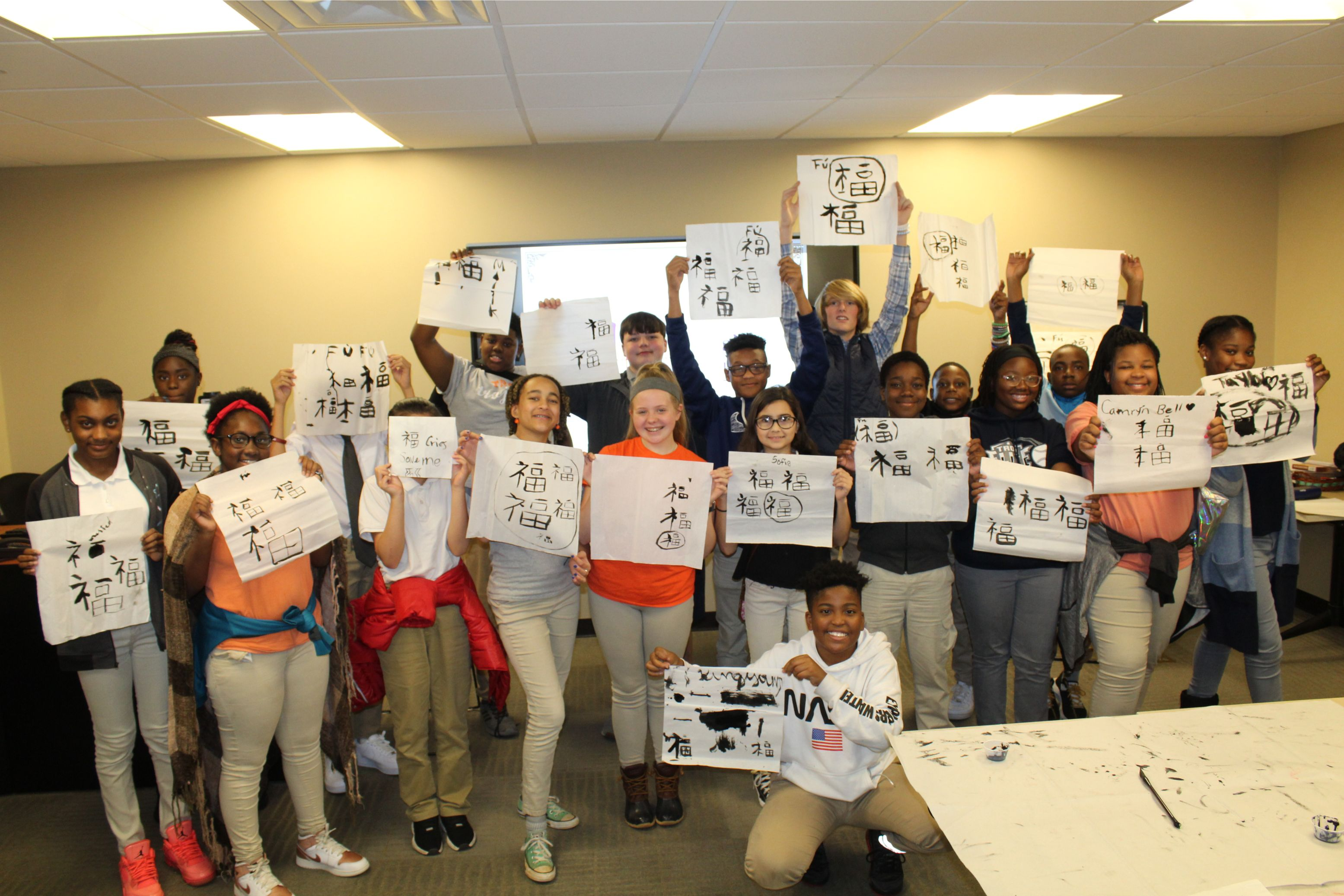 The students all pose with their calligraphy paintings.