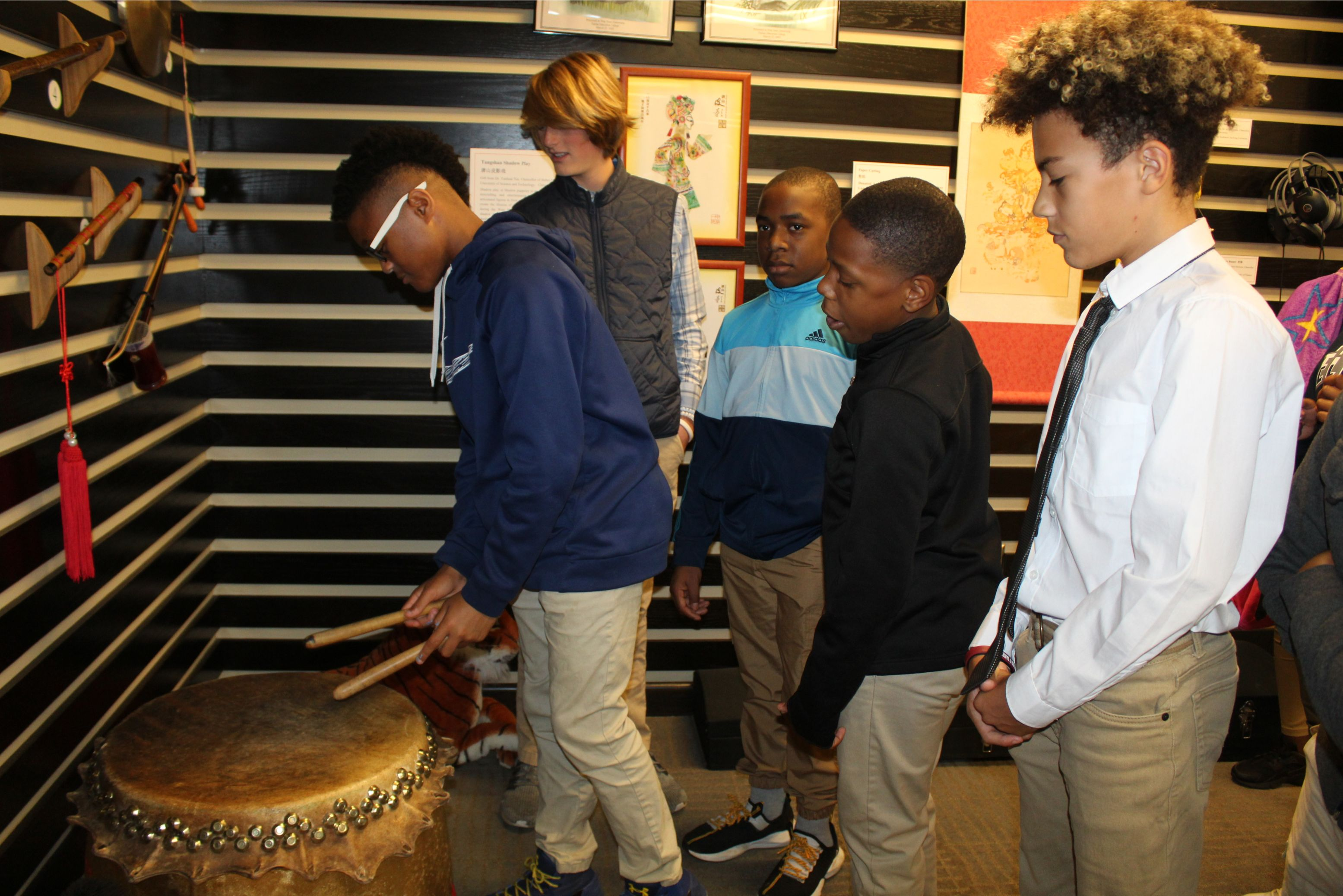 A group of boys play drums together in the exhibition hall.