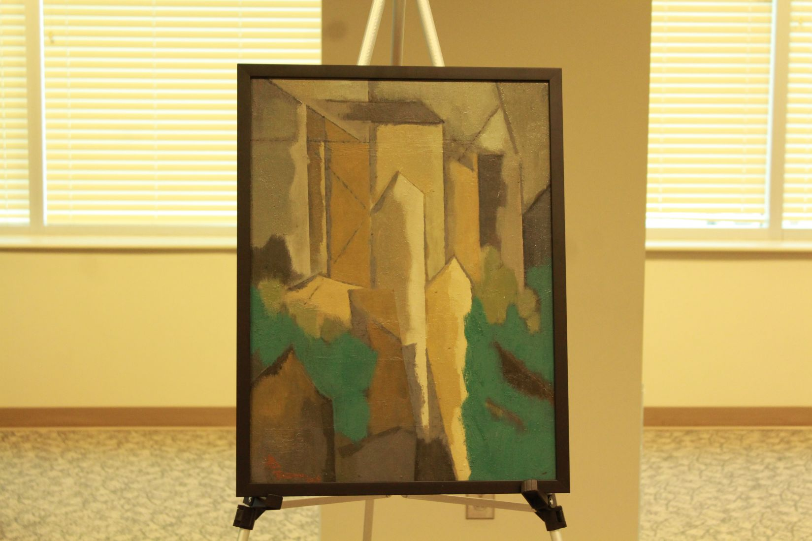 A painting hangs on an easel, angular neutral designs meeting bright teal clouds.