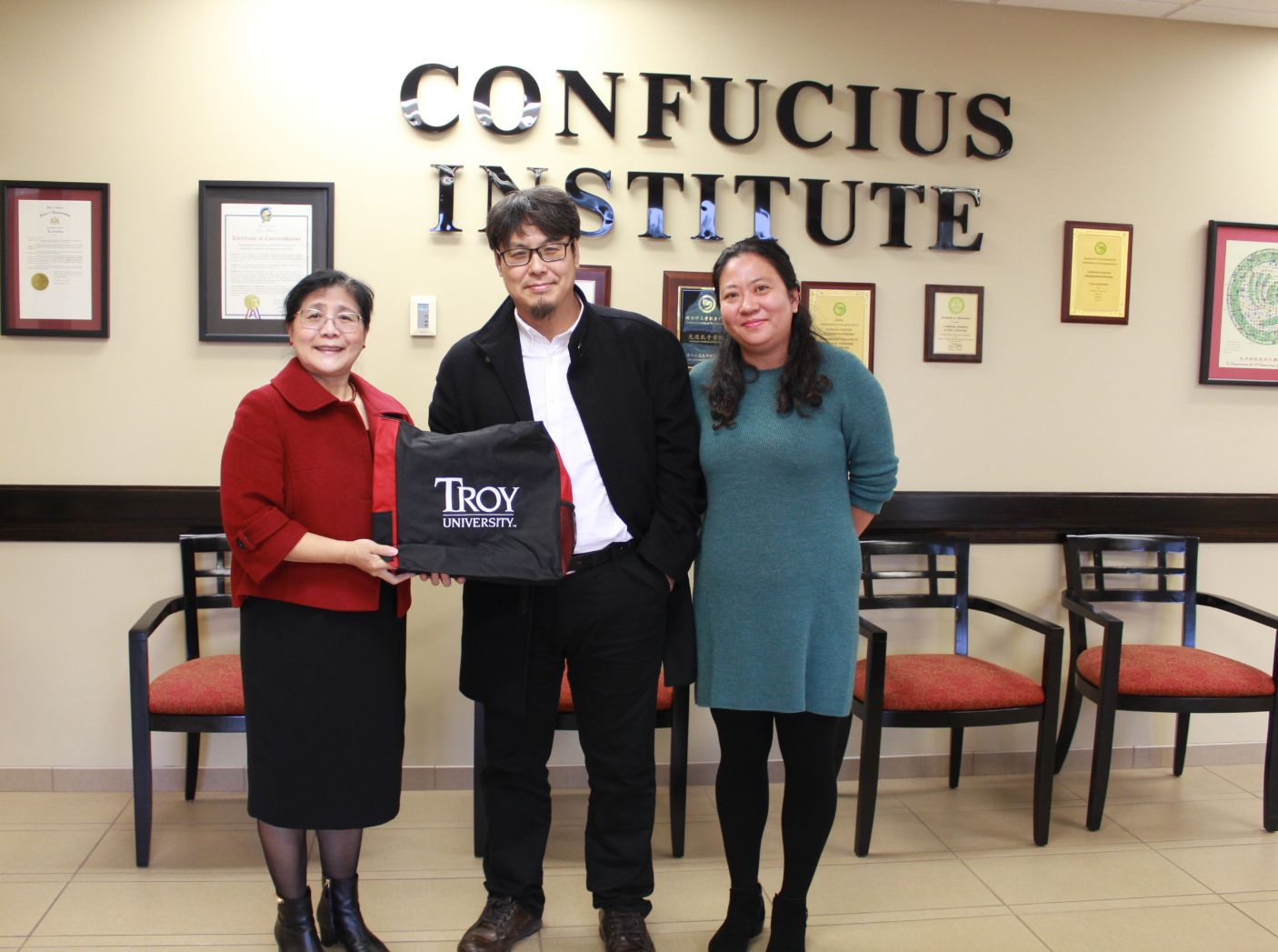 Drs. Xu and Zhang of the Confucius Institute at Troy University pose with the artist Zhou Tao.