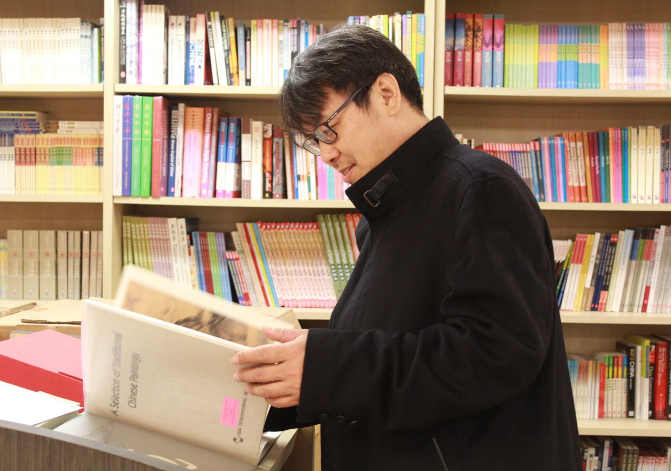 Tao explores the CIT library, reading a book off the shelf.