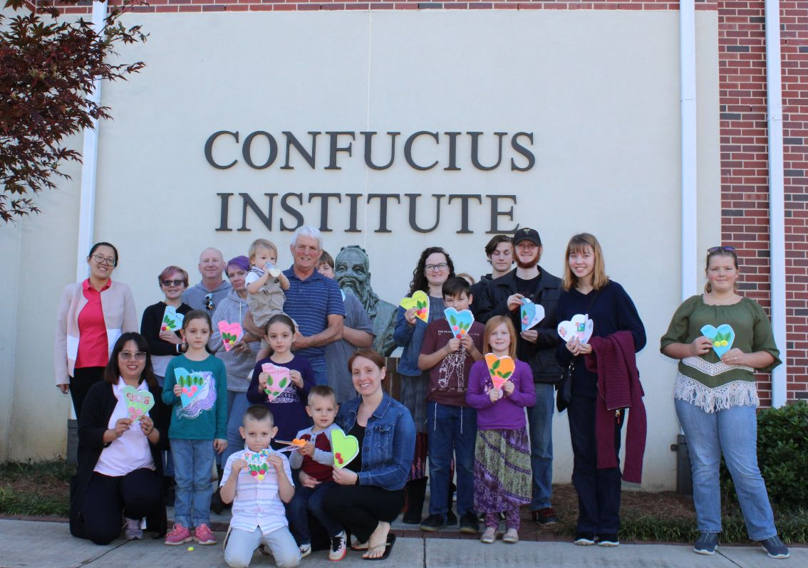 The children and parents pose outside the CIT with the Confucius statue.