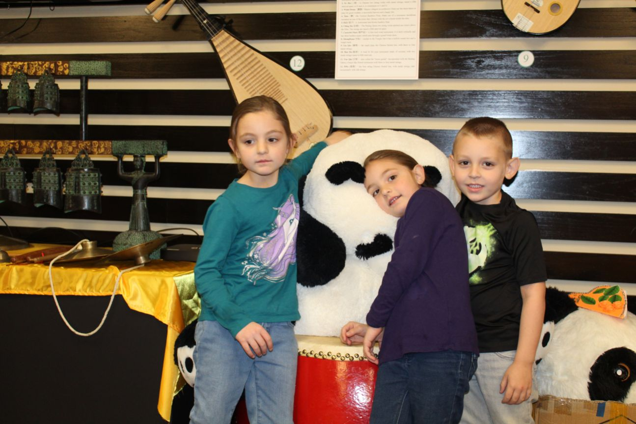 Three little kids cuddle up with the giant panda stuffed animal in the exhibition center.
