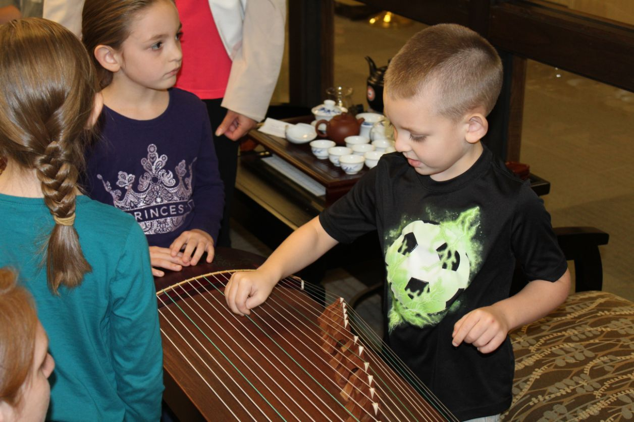 One little boy tries to play the guzheng while other children wait for their turn.