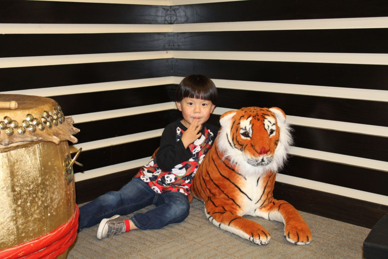 Another little boy cuddles with a tiger stuffed animal in the exhibition center.