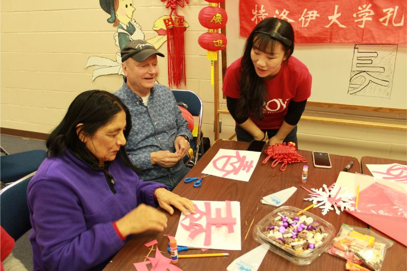 "A visiting scholar helps the guests write the Chinese character ""Chun."""