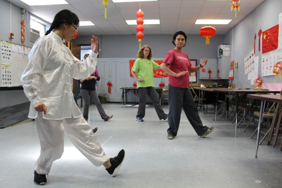participantss practiced taichi moves after the instruction of the visiting scholar