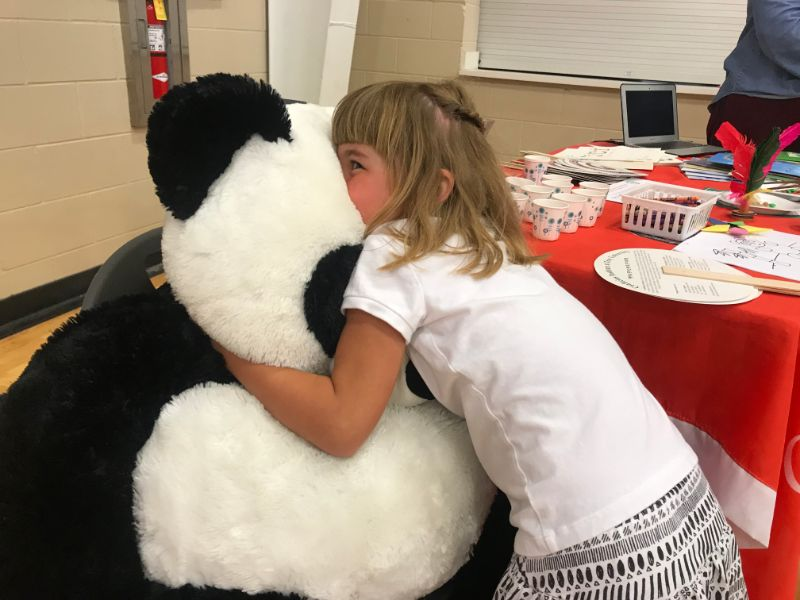 a little girl took picture hugging panda plushie