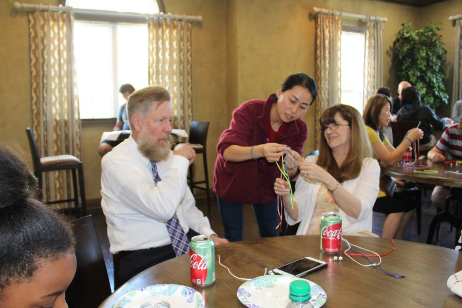 a visiting scholar showed a participant how to make chinese bracelet