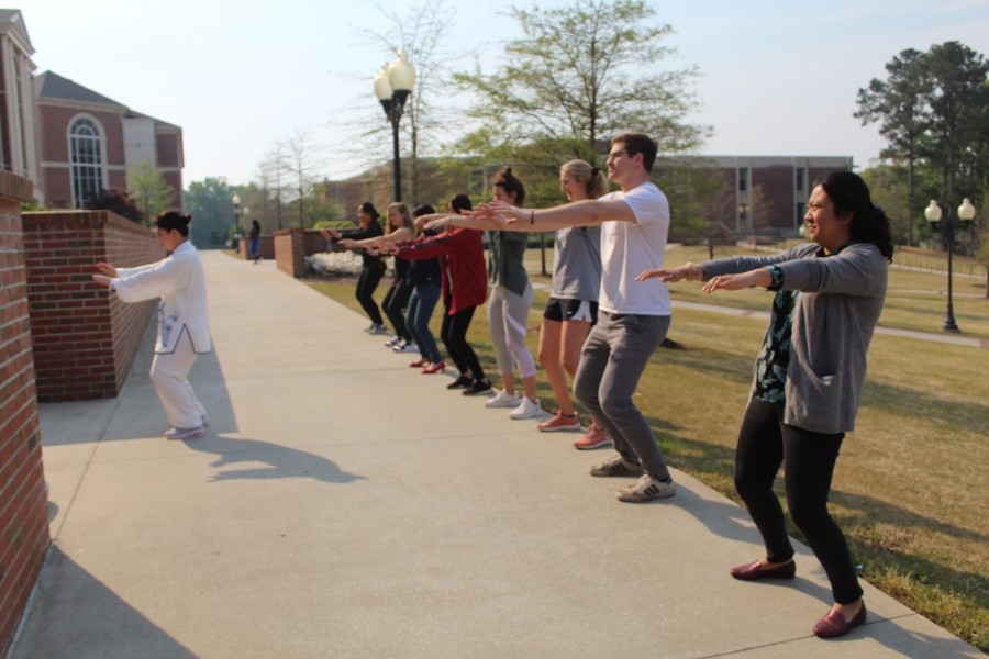 troy students practiced taichi moves after the instruction of Li Wei