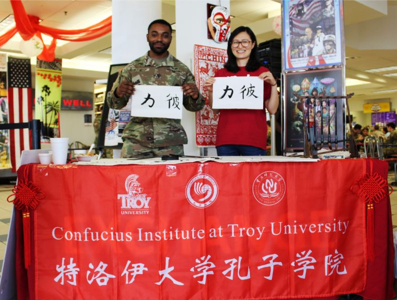 a soldier prouldy present his chinese caligraphy he just learned