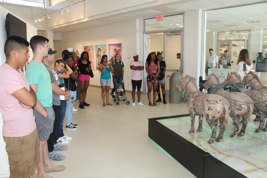 A group picture of everyone gathered around Horses Statues in Horeses Museum.