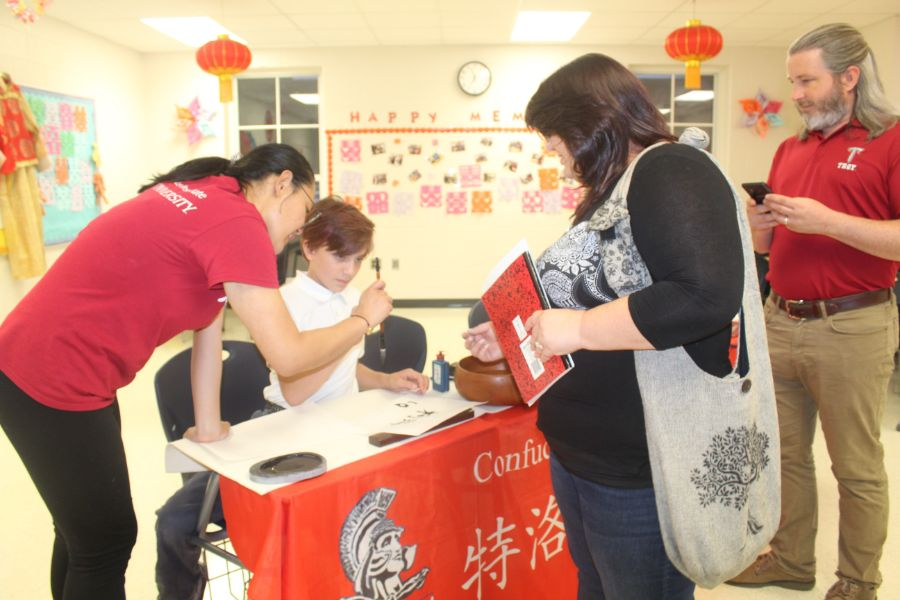 Visiting scholars teach children Chinese calligraphy, while parents observe.