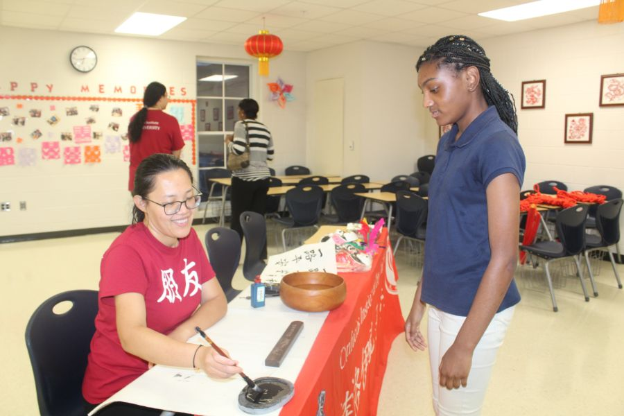 Confucius Institute members write student names in Chinese calligraphy.