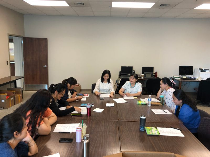 Dr. Xu and Visiting Scholars gather around a table to plan the upcoming events.