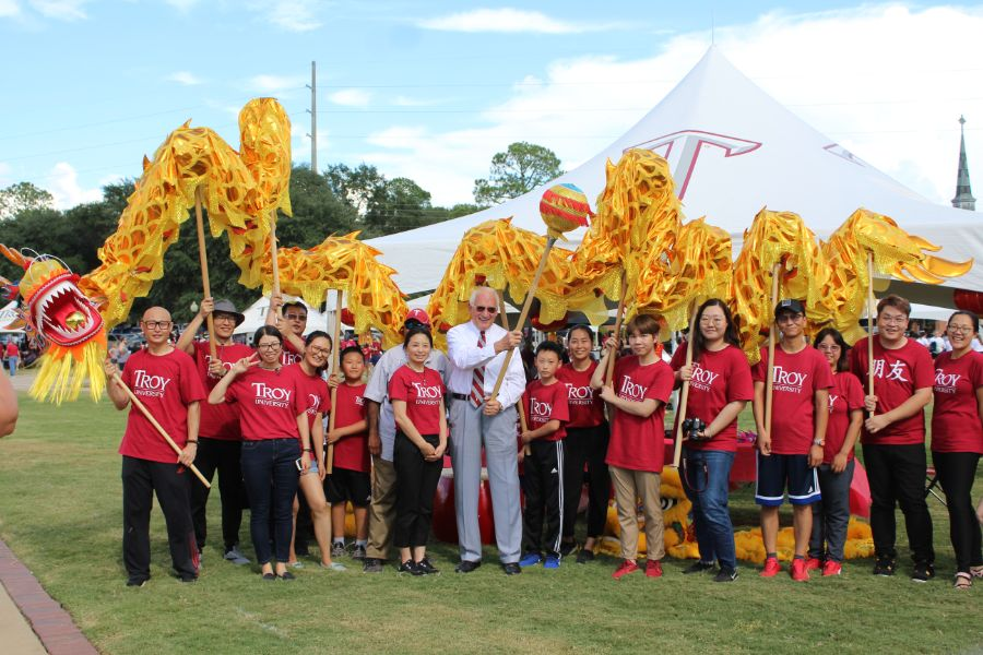 Chancellor Hawkins joins the Confucius Institute scholars and staff in front of a Chinese dragon.