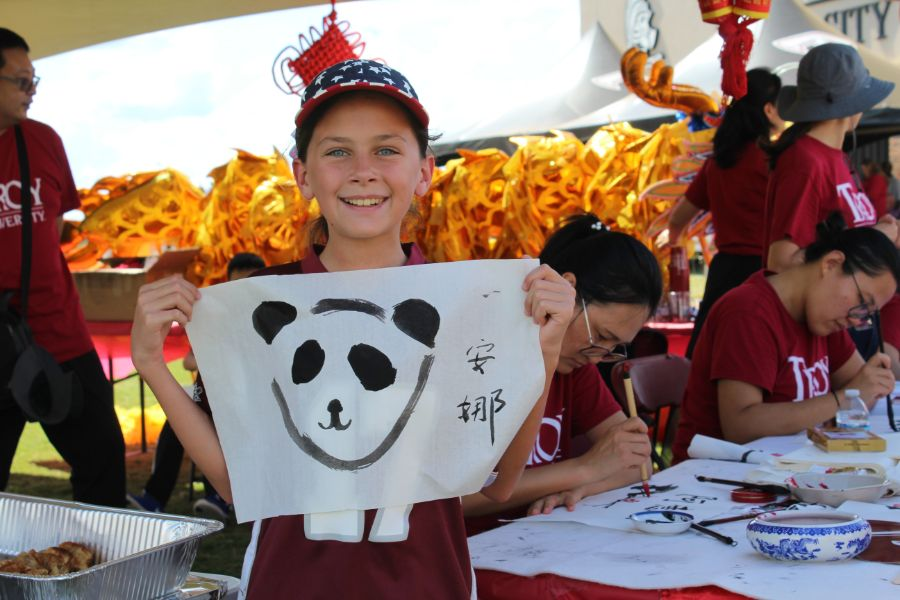 Young tent visitor proudly displays his panda painting and Chinese calligraphy.