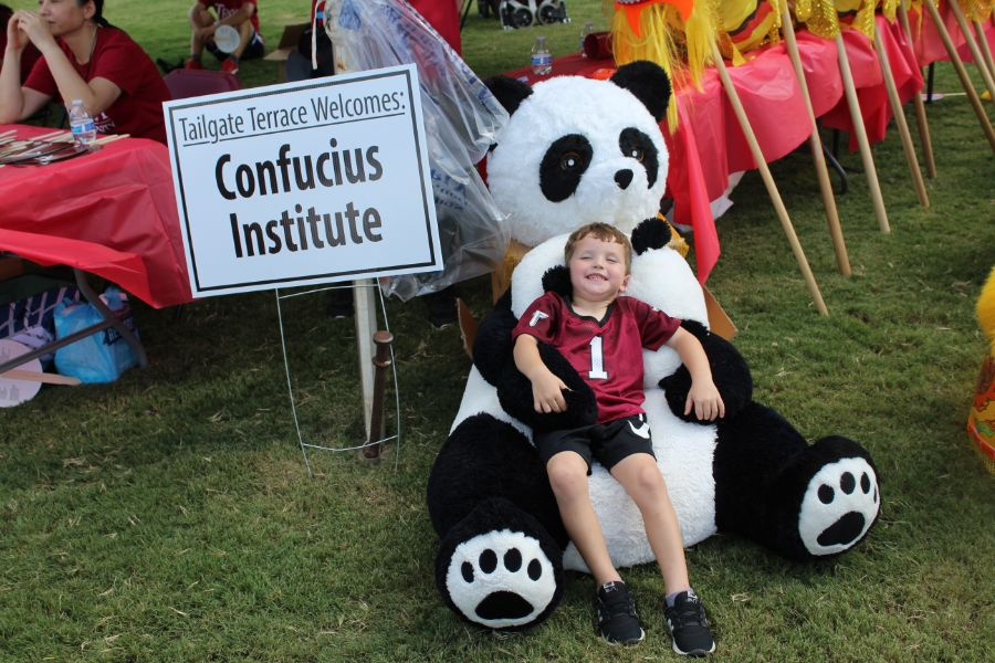 Child guest cuddles up with the Confucius Institute's stuffed panda bear.