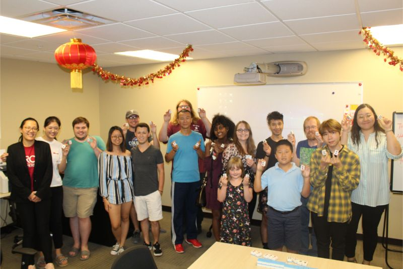 Guests join CIT Scholars for group photo at Mahjong-themed Chinese Tea Talk.