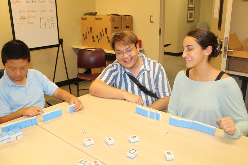 Troy community students have fun and laugh together while playing Mahjong.